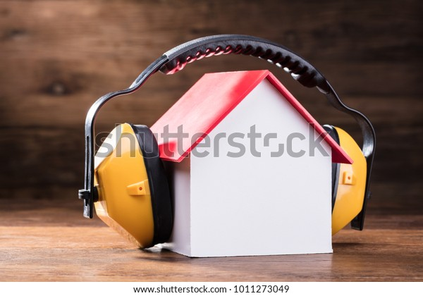 Cierre De Los Auriculares Protectores Amarillos En El Modelo De La Casa Sobre La Mesa De Madera