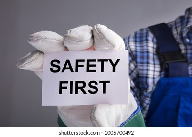 Close-up Of Workman Hands With Gloves Showing Safety First Sign