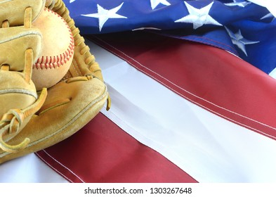 Closeup of worn baseball and mitt on a US flag background, great for America's favorite pasttime. Copy space.
