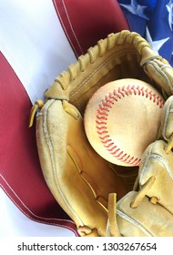 Closeup of worn baseball and mitt on a US flag background, great for America's favorite pasttime. Vertical composition