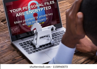 Close-up Of Worried Businessman Encrypted Text On The Laptop Over The Wooden Desk