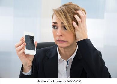 Close-up Of Worried Businesswoman Holding Broken Screen Smartphone In Office