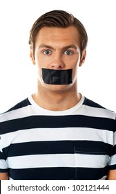 Closeup of a worried man. Mouth covered with duct tape