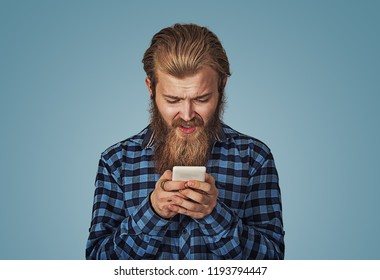 Closeup worried sad man looking at his smart phone. Hipster male with beard in blue plaid checkered shirt  Isolated on gray studio Background. Negative face expression, human emotion, body language.