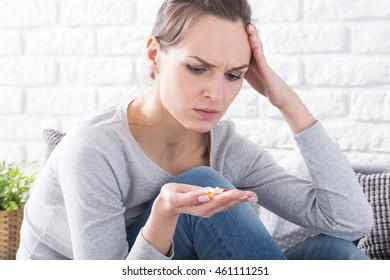 Close-up of worried young woman holding drugs on hand