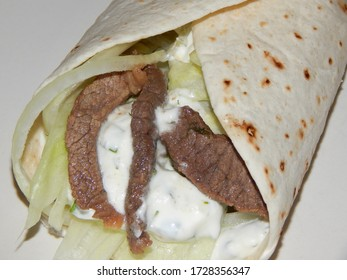 Closeup of a wrap snack with juicy fried beef, salad and sour creme