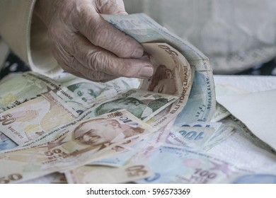 closeup of a wrinkled hand counting turkish lira banknotes