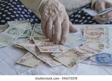 closeup of wrinkled hand counting turkish lira banknotes