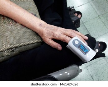 Closeup of wrinkled hand of old patient sit on wheelchair with fingertip pulse oximeter.