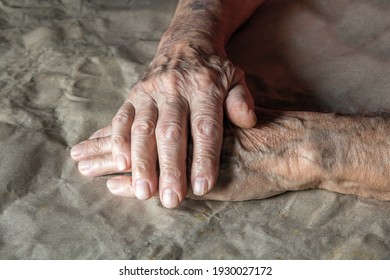 Close-up of the wrinkled hands of an elderly man, old mans hands resting on the table, paper background