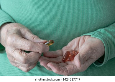 closeup wrinkled hands of a senior woman holding vitamin pills on her palm