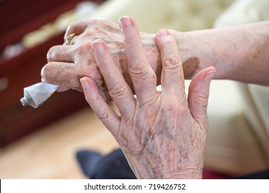Close-up of wrinkled woman's hands applying cream from tube.