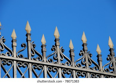 Close-up of a wrought iron fence over a blue sky