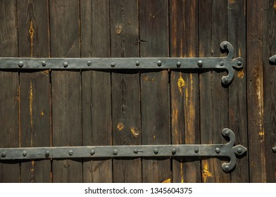 Close-up of wrought iron hinge with studs in an old wooden door in a sunny day at Elvas. A gracious star-shaped fortress city on the easternmost frontier of Portugal.