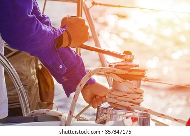Closeup up of Yachtsman hands dealing with yacht ropes .Lens flare, unrecognizable person