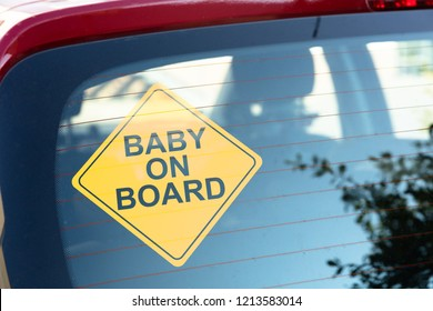 Close-up Of Yellow Baby On Board Sticker On Car Back Window