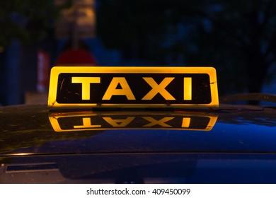 Closeup to a yellow and black taxi sign on a top of a car. Reflections can be seen on the car roof.
