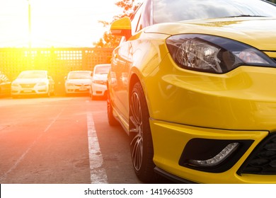 Close-up yellow car parked neatly inside an outdoor parking lot.