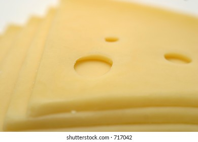Closeup of yellow cheese slice with three holes
