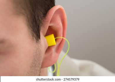 Close-up Of Yellow Earplug Into The Ear Of Person
