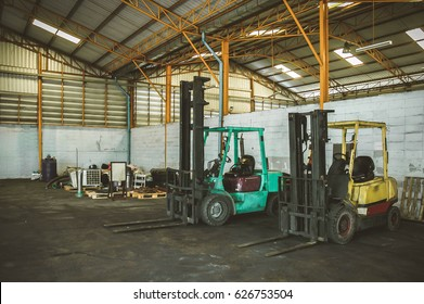 close-up of a yellow forklift, with no driver, parked inside an industrial hall, with green industrial machinery and a roll of metal sheet in the background