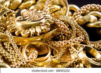 Closeup of yellow gold jewelery on a black background