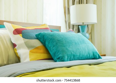 Closeup yellow and green pillows on bed in modern interior bedroom