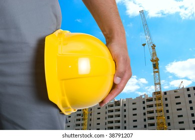 Closeup of yellow helmet at builder hands on building background