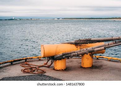 Close-up of yellow metallic mooring column or bollard on the edge of stone quay blue water background. Marine Bollard column with eye-splice on the end of rope. Loop in the end of a rope.