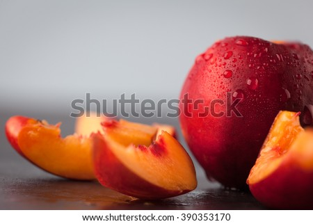 Closeup of yellow nectarine peach slices and whole fruit with water drops. Copy space. Shallow depth of field.
