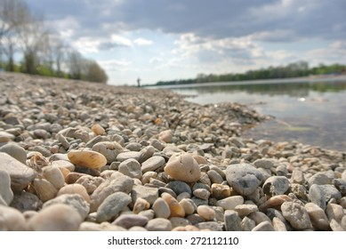 Closeup of yellow pebbles on the lake shore on a sunny summer afternoon; low angle shot. Personal pov.
