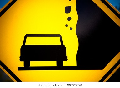 Close-up of a yellow sign with a car silhouette and falling rocks
