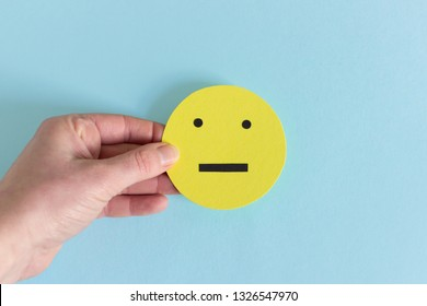 Closeup of yellow smiley with emotion of indifference and indecision in crop hand on blue background