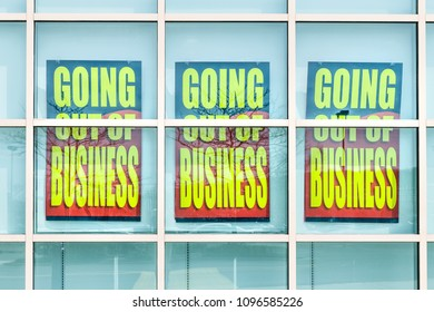 Closeup of yellow store closing banner poster sign on glass window of store building for bankruptcy going out of business