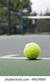 A closeup of a yellow tennis ball just outside of the base line on an asphalt tennis court, with a blurred net in the background.