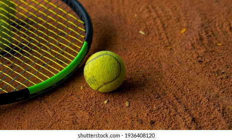 A closeup of the yellow tennis ball with a racket in the clay court