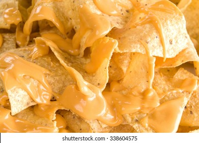 Close-up of yellow tortilla chips covered in nacho cheese
