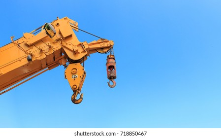 closeup yellow truck crane with blue sky background. over light