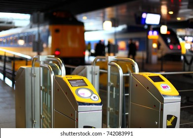 Close-up yellow turnstile or tourniquet on the railway station or underground in city center. Blurred trains, passengers and timetable screens on the background