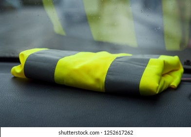 closeup of yellow vest on dashboard in car symbol of yellow vest movement