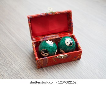 Close-up of a Yin Yang balls in a box on the wooden table, selectiva focus