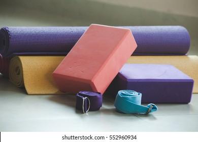 closeup of yoga blocks belts and mat props indoor