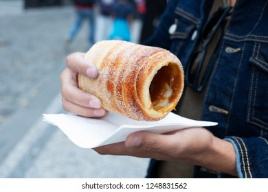 closeup of a yougn caucasian man eating a trdelnik, a typical spit cake, in the old town of Prague, Czech Republic