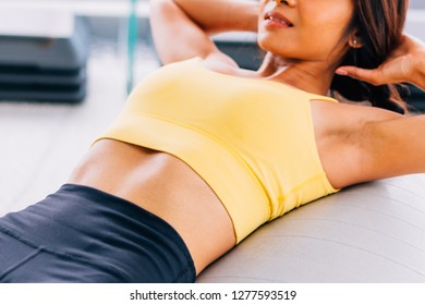 Close-up of young active and fitness Asian woman doing sit ups and crunches inside gym with exercise ball in background