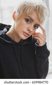 Close-up of young adult blonde woman in black hoodie