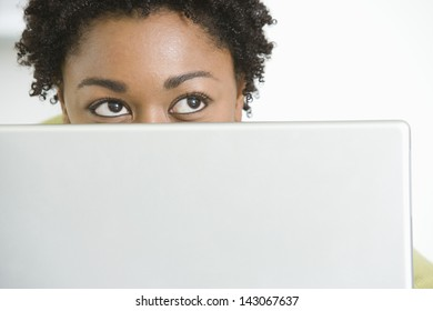 Closeup of young African American woman with laptop looking up