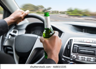 Close-up Of A Young African Businessman Holding Beer While Driving Car