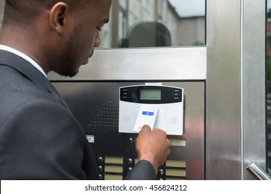 Close-up Of Young African Businessman Using Keycard To Open Door