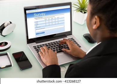 Close-up Of A Young African Businesswoman Filling Online Survey Form On Laptop