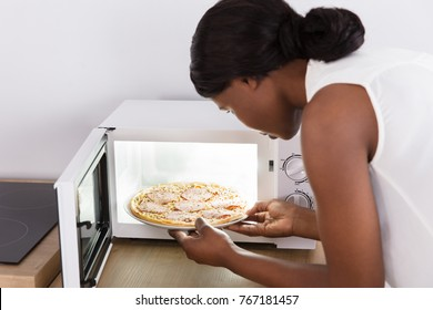 Close-up Of A Young African Woman Baking Pizza In Microwave Oven